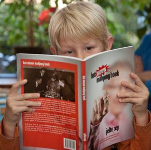 Luuk bekijkt de plaatjes in het boek.